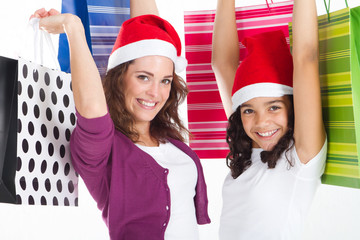excited mother and daughter with christmas hats and gifts