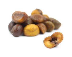 Single roasted chestnut with group of chestnuts behind