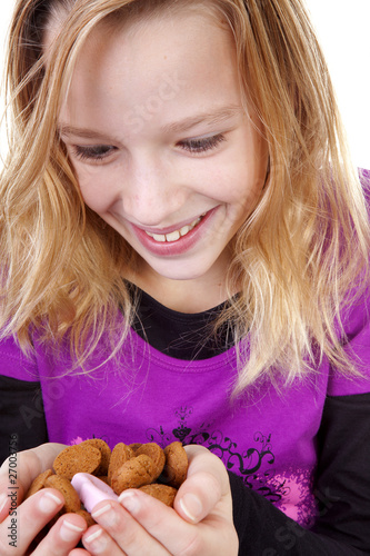 Girl with ginger nuts (pepernoten) over white background