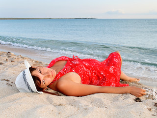 Woman in a red dress and hat on the beach