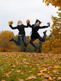 two beautiful girl friends with autumn leafs in a park jumping
