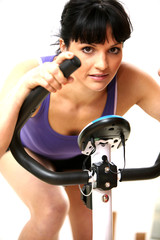 Young Woman Riding Exercise Bike. Model Released