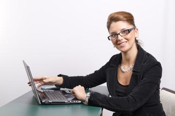 Joven ejecutiva trabajando con portátil