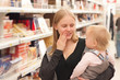 young mother and toddler girl shopping pies in supermarket