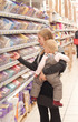 young mother and toddler girl shopping chocolate in supermarket