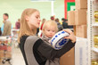 young mother and toddler girl shopping cookies in supermarket