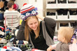 young mother and toddler girl shopping hats in supermarket
