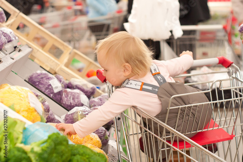 toddler girl sit in shopping cart in supermarket