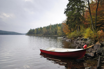 Rainy lake landscape with red boat