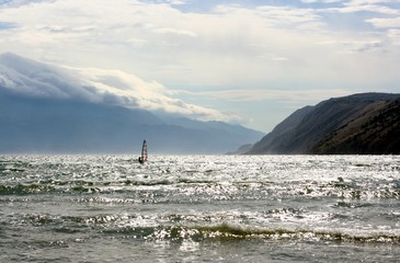 Windsurfer on a sea, mountains and clouds as a background