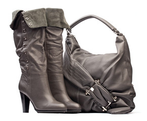 Gray female high-heeled boots and bag on white