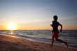 Teen boy runs at the beach on beautiful summer sunset