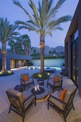 Lit firepit with chairs on terrace of California home