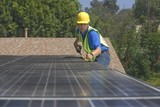 Maintenance worker measures solar array on rooftop, Los Angeles, California