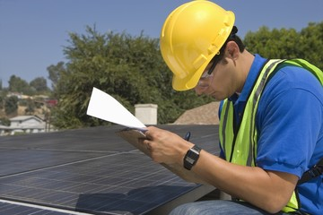 Maintenance worker makes notes with solar array on rooftop, Los Angeles, California