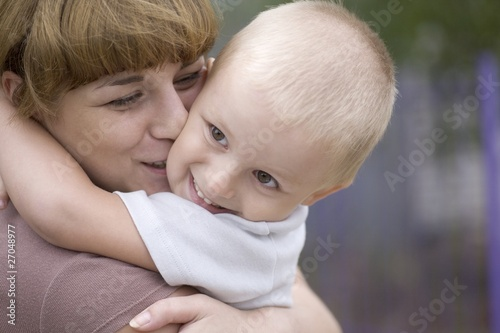 Mother kisses son aged 3-4 years