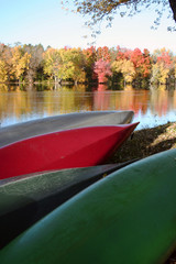 Canoes on river bank with autumn foliage