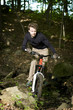 Mountain biker riding through trees downhill