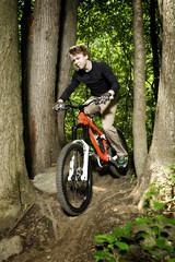 Mountain biker riding downhill through trees