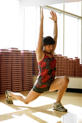 Young woman lunging in work out room