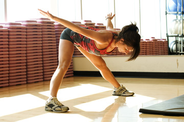 Young woman stretching in work out room