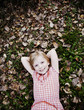 Cute Girl Laying in Fallen Leaves.