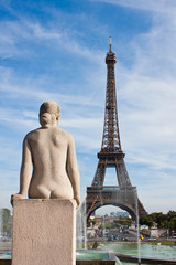 Statue of naked woman looks at Eiffel Tower