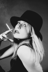 Beautiful blonde girl smoking, portrait in a studio