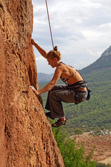 Female rock climber battling her way up
