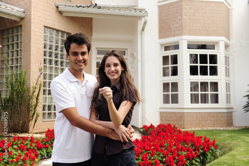 Happy homeowners infront of new house