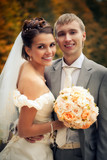 Portrait of newlyweds in autumn park
