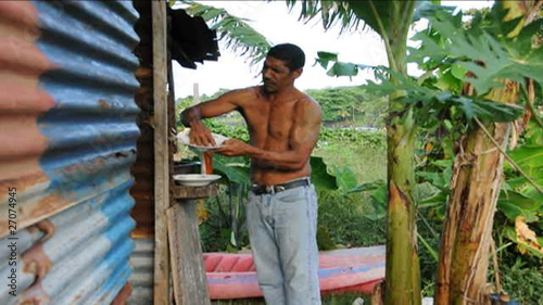 native man wash dishes zinc house Nicaragua jungle
