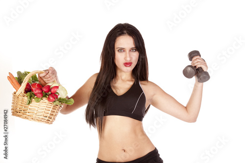 Woman holding vegetables and weights up
