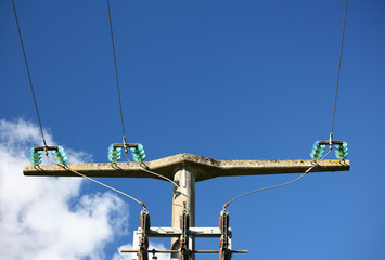 Hochspannungsleitung an Strommast vor blauem Himmel