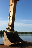 Hydraulic excavator arm with a bucket against a blue sky poster