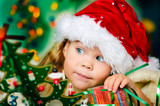 Happy small girl in santa hat have a christmas - Fine Art prints