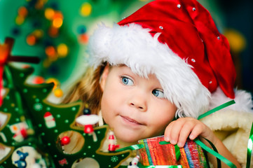 Happy small girl in santa hat have a christmas