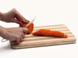 Девушка режет морковь ножом