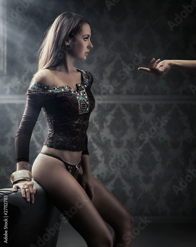 Conceptual image of young beauty following man's hand