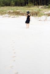Młoda piękna kobieta spacerująca po plaży