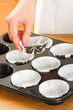 A female cook 's hand and  muffin cups in the oven pan