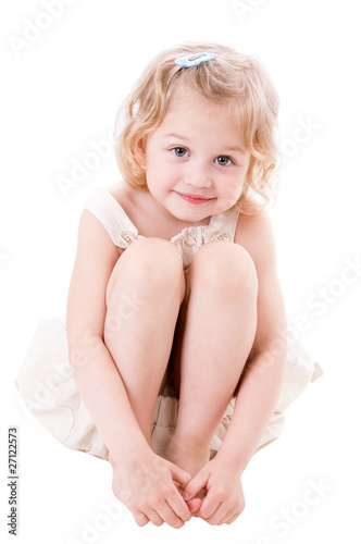Smiley little girl wearing a linen sundress sitting on white bac