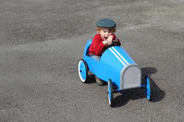 Junge in seinenem blauen Tretauto