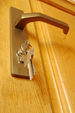 The sheaf of keys is inserted into a keyhole near to the door ha poster