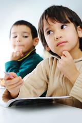 Two cute school boys working on their homework