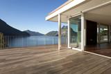 Fototapety Terrazza di casa moderna con vista su lago e montagne.