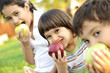 Small group of children eating apples together,