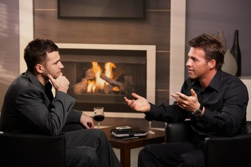 Young businessmen talking in bar