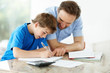 Father helping his little son in schoolwork