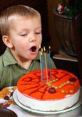 Young boy is blowing candles